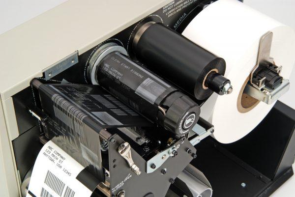 Interior de uma impressora térmica. O ribbon é este rolo preto, à direita antes da impressão e à esquerda depois de transferir a tinta para a etiqueta.