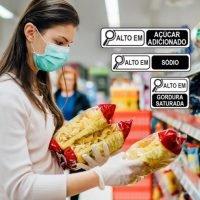 aviso anvisa mulher no supermercado olhando rótulo alimentício