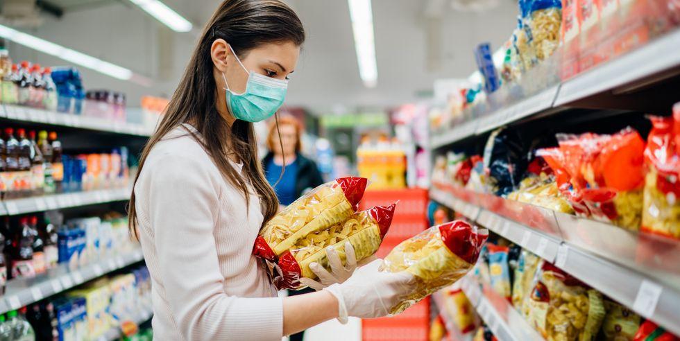 mulher no supermercado observando tabela nutricional de uma embalagem de macarrao